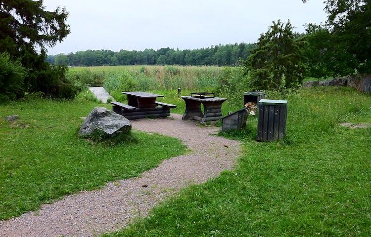 En upphöjd eldstad med grillgaller står bredvid ett bord med två bänkar. Soptunnor och vedförråd står intill. Platsen ligger nära vattnet.