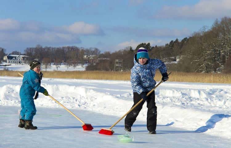 Två barn spelar curling med sopkvastar.