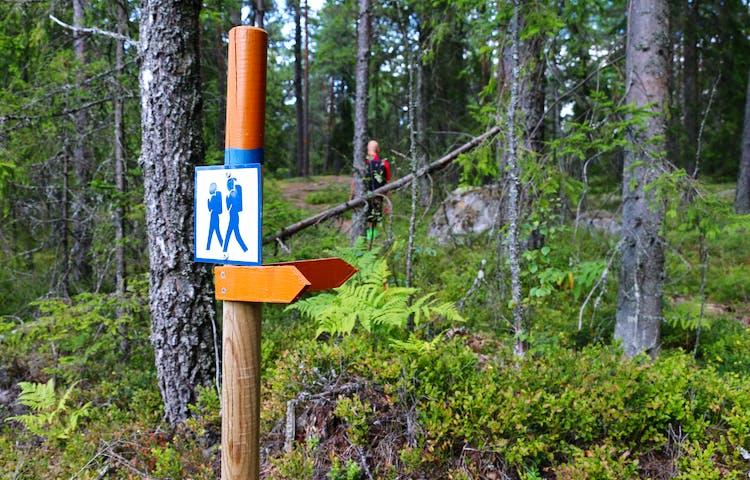 Stolpe med orange pilar som visar vägen. På stolpen sitter även en skylt som symboliserar två gående personer.