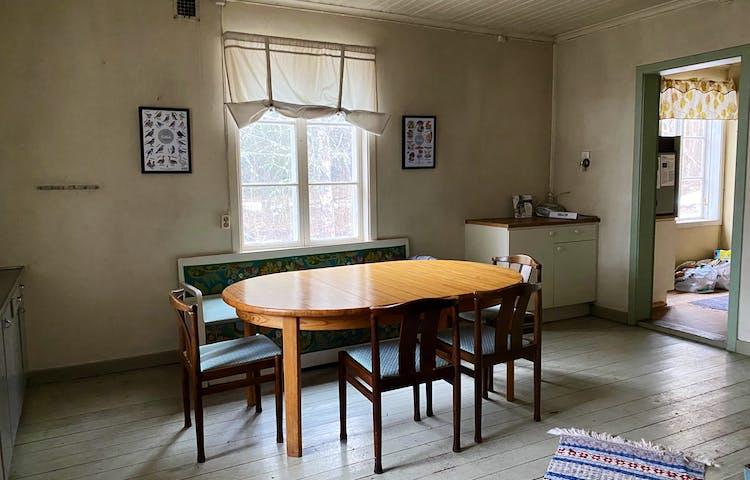 Ett kök inne i ett äldre torp. Ett bord med stolar står mitt i rummet, på golvet ligger en trasmatta och det finns ett par köksbänkar i rummet. På ena väggen hänger två tavlor.