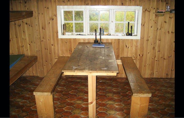 Inne i stugan: fasta bänkar och bord vid fönster.