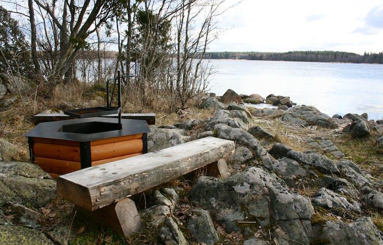 En eldstad med vridbart grillgaller ligger på klipporna nära vattenkanten. Två stockbänkar står intill.