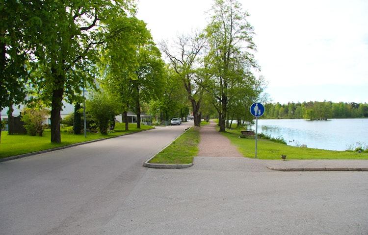 Grusad gångväg bredvid bilväg. Intill gångvägen ligger ån.