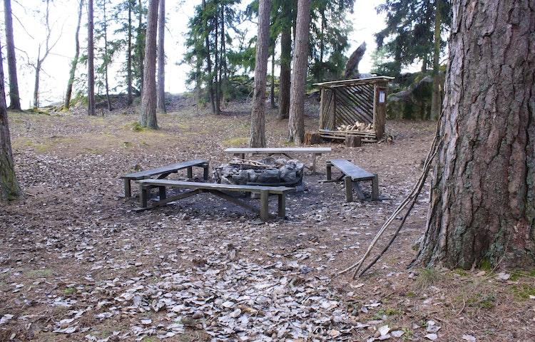 En eldstad med fyra bänkar. Ett vedförråd står cirka tio meter bort.