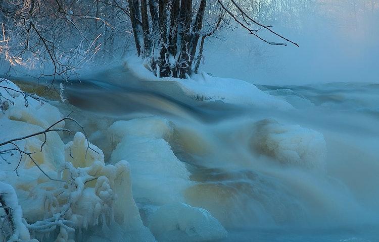 Vattnet forsar fram genom ett vinterlandskap med snö och is.