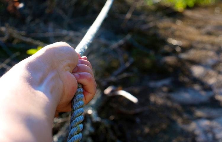 Hand som drar i ett rep.