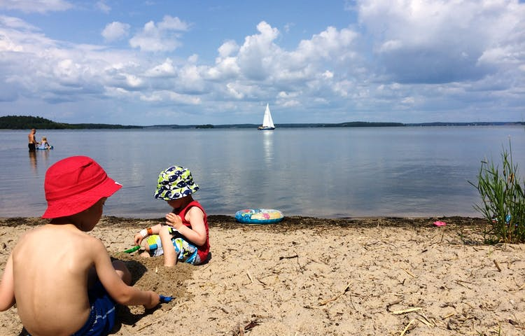 Barn leker på stranden och i vattnet. En segelbåt syns i bakgrunden.