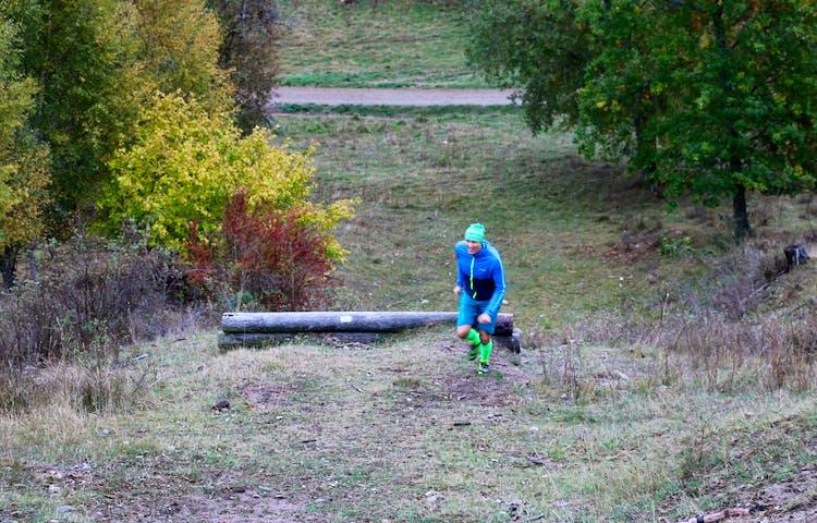 En person kommer joggande uppför en backe.