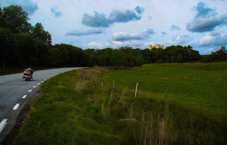 Landsvägen på Bogesundslandet med en motorcykel. Över träden sticker Bogesunds Slott upp.