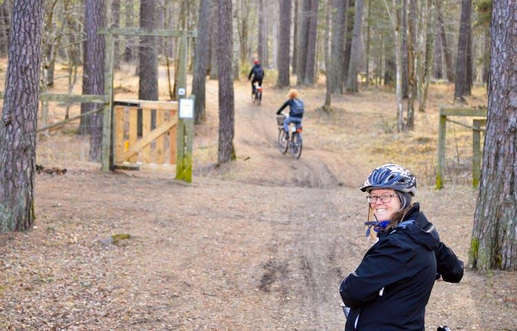 En kvinna med cykelhjälm leder cykeln på leden genom tallskogen.