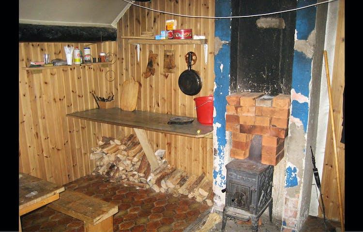 Inne i stugan: arbetsbänk och kamin.