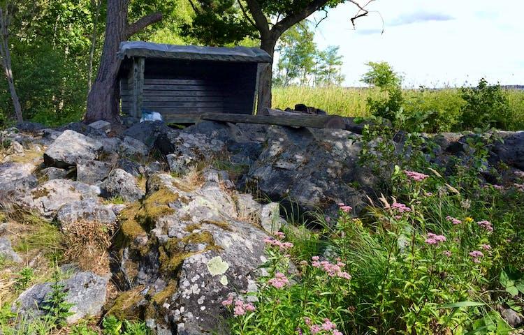 Vindskydd med stenar i förgrunden.