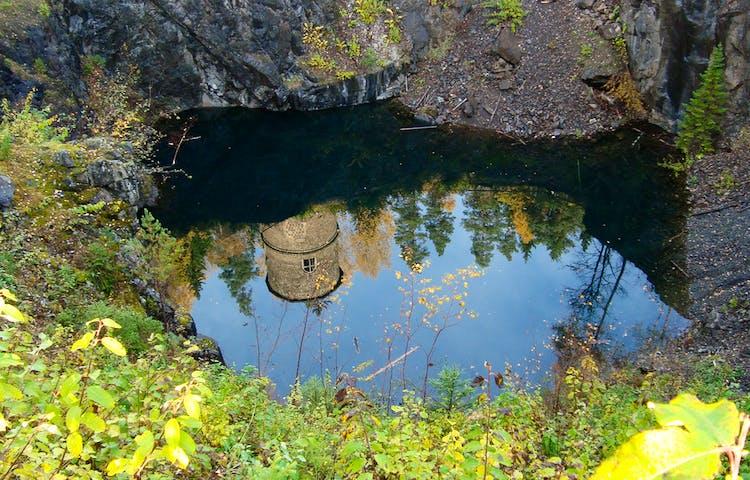 En lave byggd av slaggsten speglar sig i ett dagbrott fyllt av vatten.