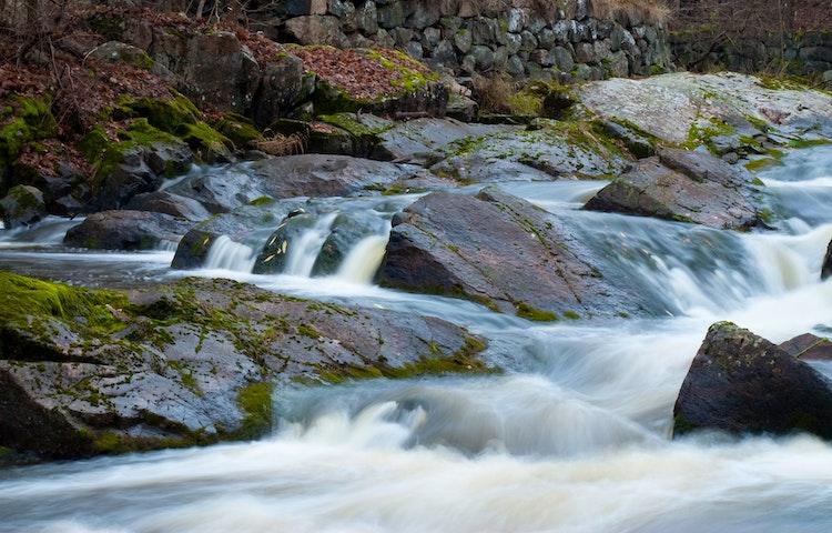 Vattnet forsar runt stenar.