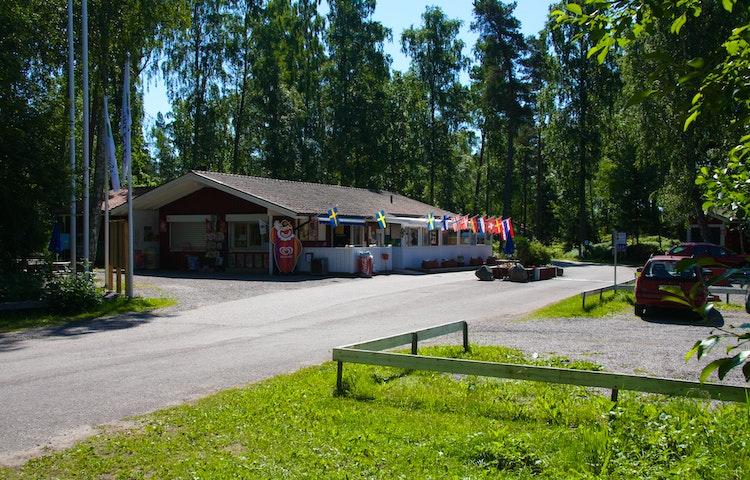 En asfalterad väg leder fram till campingbyggnaden. På andra sidan vägen finns en parkeringsplats med grus och lite gräs på marken.