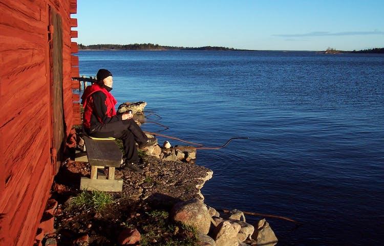 En person sitter på en bänk vid en strandbod. Vattenkanten ligger precis vid personens fötter.