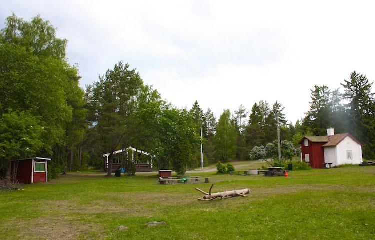 Tre stugor med en stor gräsyta omringad av lövträd. Flera bänkar och bord står på gräset.