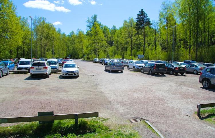 Stor parkering med många bilar.