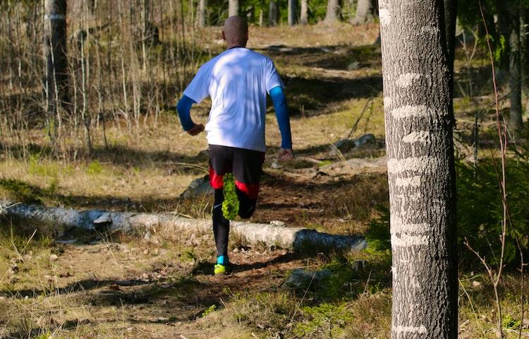 En person springer fram över stock och sten.