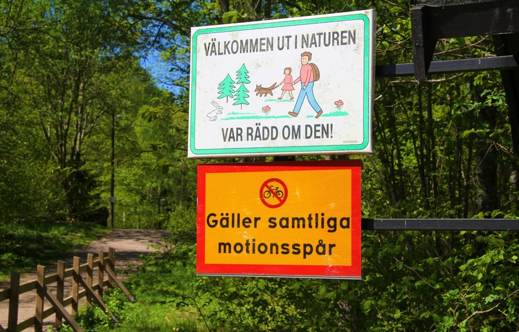 Skyltar som säger att det är cykelförbud i motionsspåren och att man ska vara rädd om naturen.