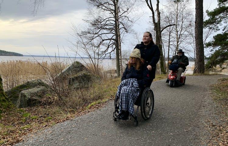 Hårdgjord stig med två personer i rullstol och en ledsagare. Två stora stenar på vänster sida med vatten i bakgrunden.