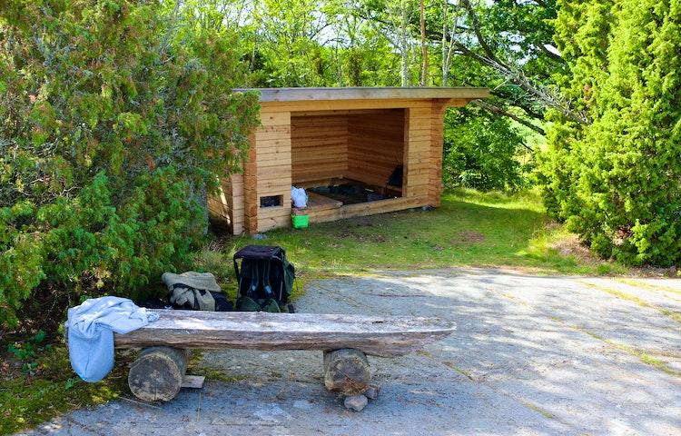 Vindskydd i skogsglänta. Framför vindskyddet står en bänk att sitta på.