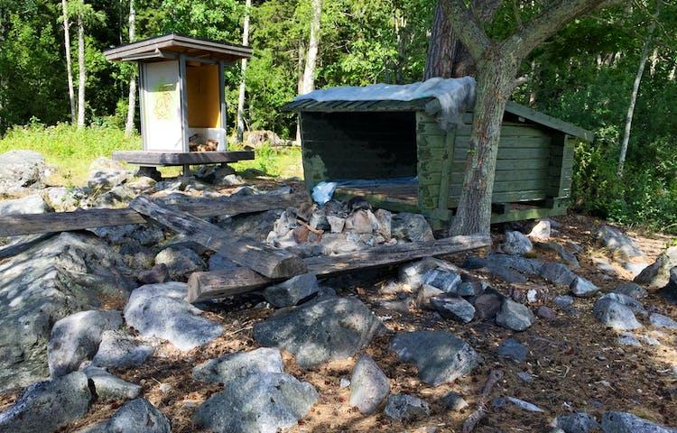 Vindskydd, eldstad och vedbod i stenig miljö.