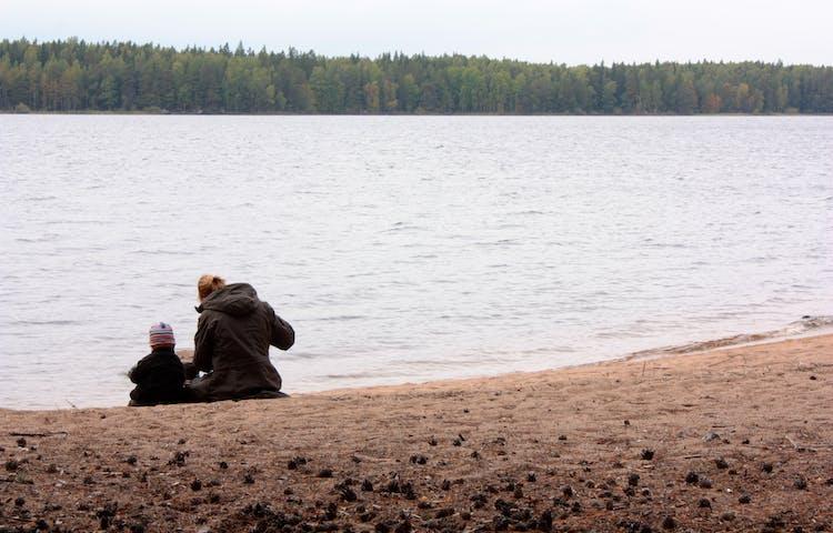 En vuxen och ett barn sitter bredvid varandra på en sandstrand vid vattnet