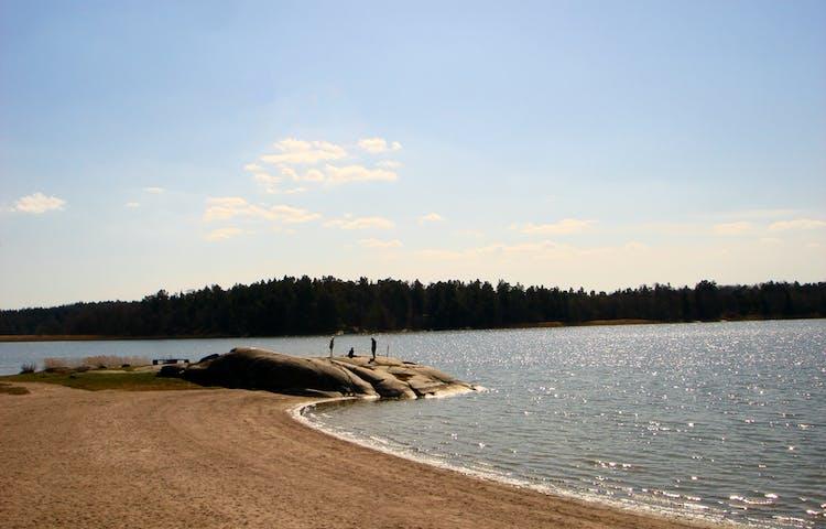 En sandstrand med glittrande vatten och klippor längst bort.